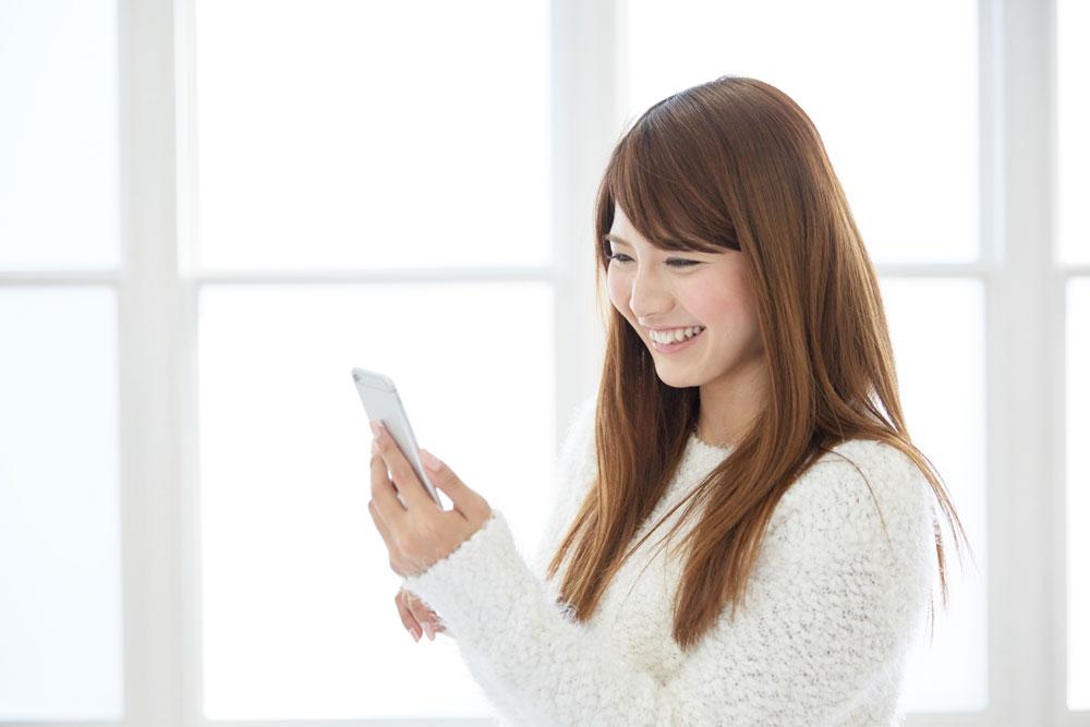 スマホで英語のアプリを触る女性